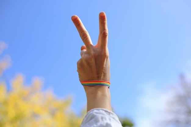 A mão fêmea com pulseira do arco-íris mostra o sinal da vitória no backgroung do céu azul. conceito lgbt