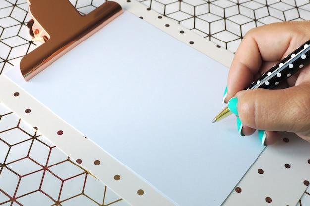 A mão fêmea escreve com uma pena de esferográfica em uma folha de papel limpa em uma prancheta. fundo geométrico.
