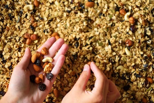 A mão fêmea guarda o granola na perspectiva da folha de cozimento com granola. comida para o café da manhã. fundo de refeição e textura macro