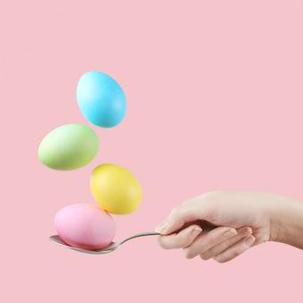 A mão fêmea guarda uma colher em que os ovos multi-coloridos são equilibrados, em um fundo cor-de-rosa. projeto incomum, conceito de páscoa, copie o espaço.