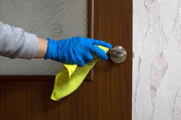 A mão fêmea na luva de borracha azul limpa a maçaneta com guardanapo amarelo. desinfecção da maçaneta da porta da sala