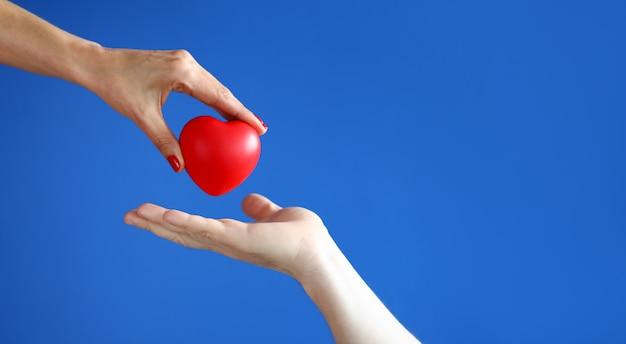 A mão fêmea passa o coração vermelho à mão masculina contra o close up azul do fundo.