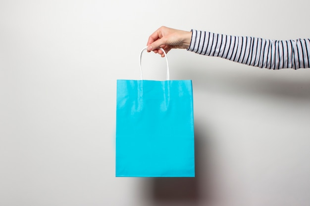 A mão fêmea prende uma sacola de compras em um branco. conceito de compras, desconto, venda.