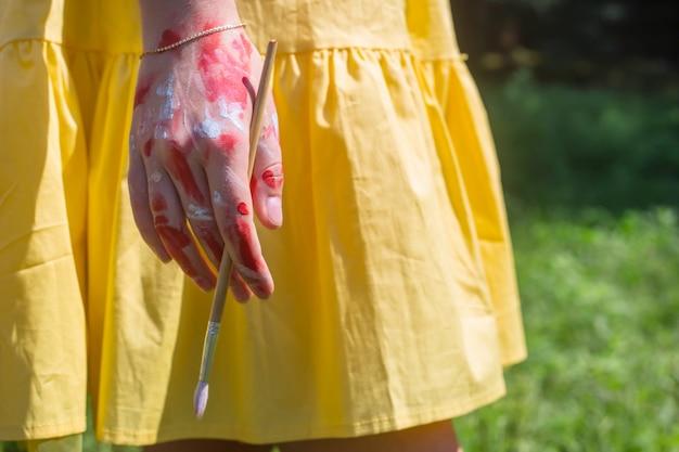 A mão feminina do artista manchada de tinta segura uma escova. conceito de arte.