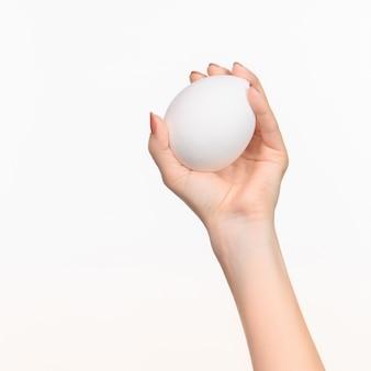 A mão feminina segurando uma figura oval de isopor em branco contra o branco com sombra à direita