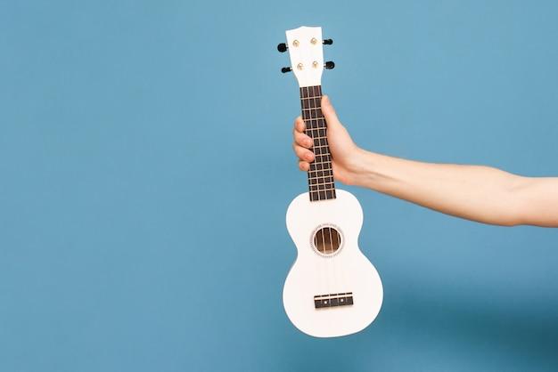A mão guarda a uquelele em um fundo azul. conceito musical. música como hobby.