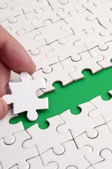 A mão humana abre o caminho para a superfície do quebra-cabeça, formando um espaço verde