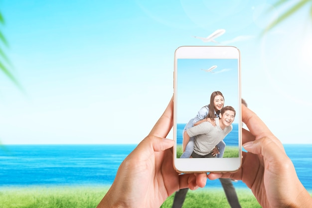 A mão humana com o celular tirando uma foto de um casal asiático viajando no campo com o fundo da paisagem marinha