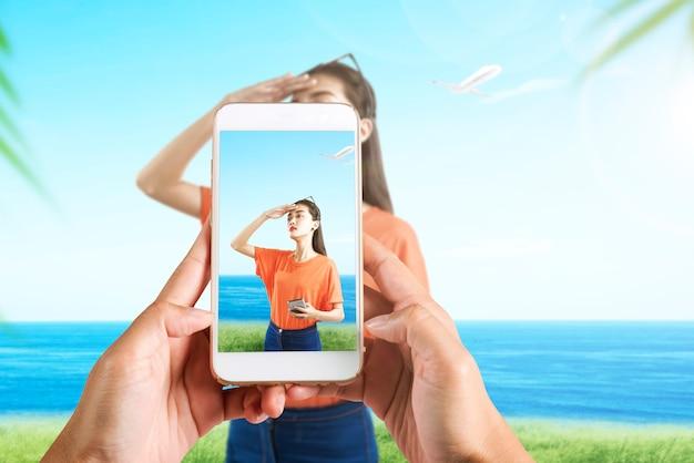 A mão humana com o celular tirando uma foto de uma mulher asiática viajando no campo com o fundo da vista do mar