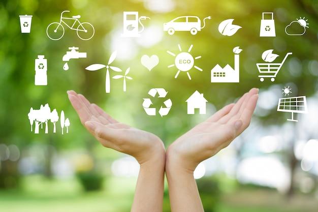 A mão humana está segurando ícones ecológicos no verde, salvar o conceito de terra.