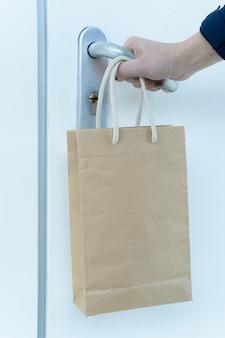 A mão humana está tentando abrir uma porta trancada e um saco de papel com comida está pendurado em seu pulso.