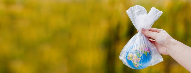 A mão humana segura o planeta terra em um saco plástico. o conceito de poluição por detritos plásticos. aquecimento global devido ao efeito estufa.