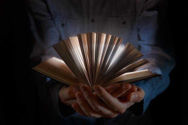 A mão humana segura um livro mágico com luzes mágicas