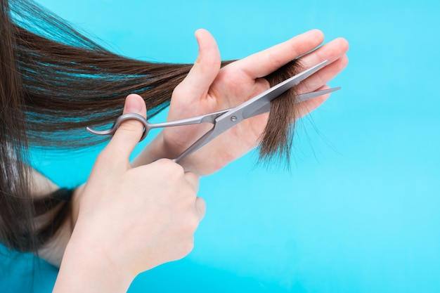 A mão infantil corta as pontas dos cabelos em um fundo azul.