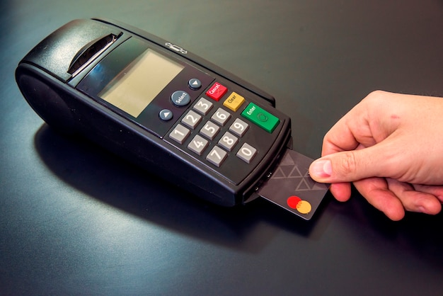 A mão macho marca o código pin na almofada de pinças da máquina de cartão ou pos terminal com o cartão de crédito em branco inserido isolado no fundo branco. pagamento com cartão de crédito - empresário segurando pos terminal.