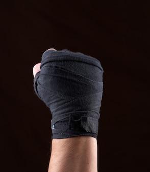 A mão masculina é envolvida em uma atadura preta de matéria têxtil dos esportes