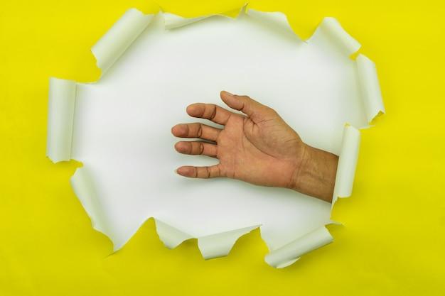 A mão masculina rasgou o papel amarelo no fundo branco, espaço para sua mensagem no papel rasgado.