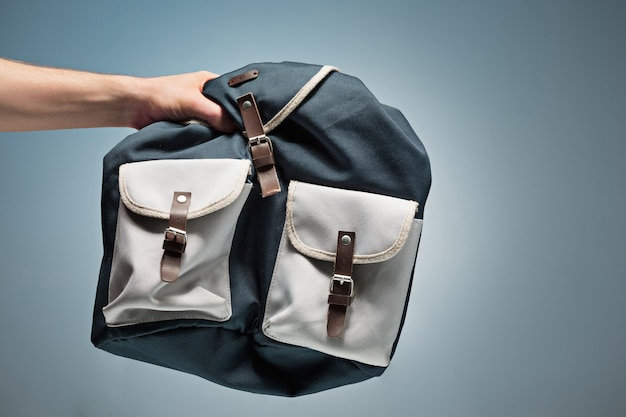 A mão masculina segurando sua mochila