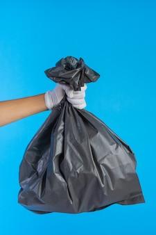 A mão masculina segurando um saco de lixo e um azul.
