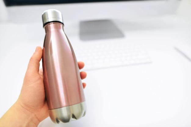 A mão masculina tira da mesa de escritório uma eco garrafa térmica de aço para água. garrafa de água de metal.