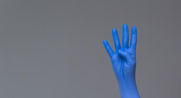A mão na luva cirúrgica mostra quatro dedos no fundo neutro. copie o espaço.