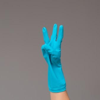 A mão na luva cirúrgica mostra três dedos no fundo neutro. copie o espaço.