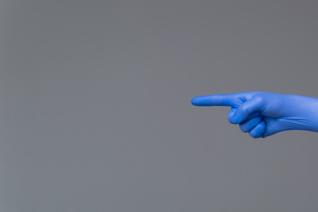 A mão na luva de borracha aponta para a esquerda com o dedo indicador. fundo neutro, cópia espaço.