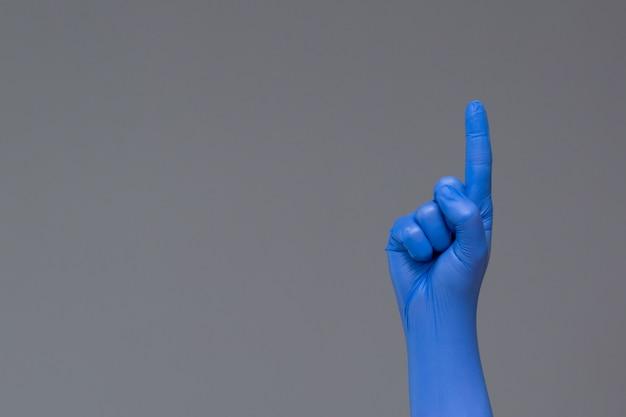 A mão na luva de borracha aponta para cima com o indicador, copyspace.