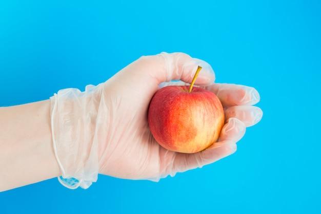 A mão na luva médica segura a maçã vermelha sobre o fundo azul. concepção de entrega segura