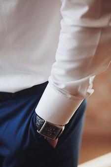 A mão no bolso de close-up de calças elegantes. um jovem bem-sucedido que é empresário, empresário, relógios caros, vestindo uma camisa branca simples. .