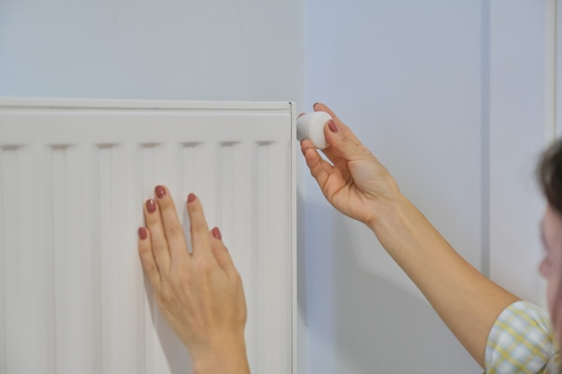 A mão no radiador de aquecimento regula a temperatura com o regulador do termostato