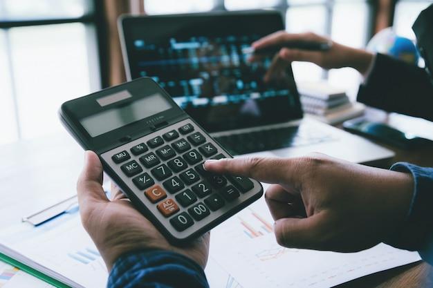 A mão nova do homem de negócios que guarda o uso irreconhecível das finanças da calculadora calcula sobre o custo no escritório.