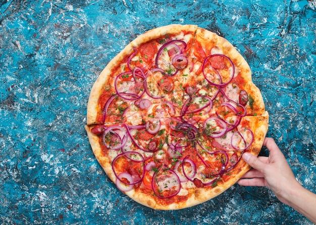 A mão pega um pedaço de pizza caseira em concreto azul. vista do topo