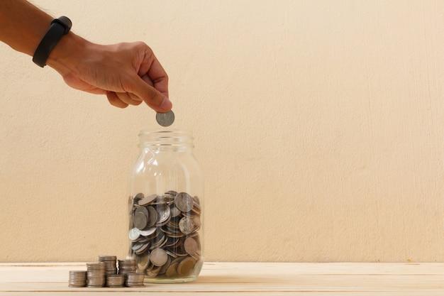 A mão põe a moeda dentro ao frasco de vidro finanças, conceito da economia. salvando o conceito de dinheiro.