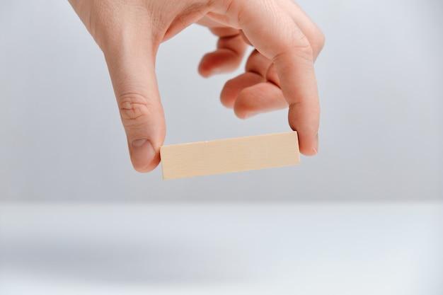 A mão prende o bloco de madeira em um espaço em branco. copie o espaço.