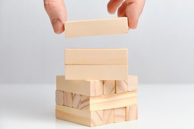 A mão prende três blocos de madeira em um espaço em branco. copie o espaço.