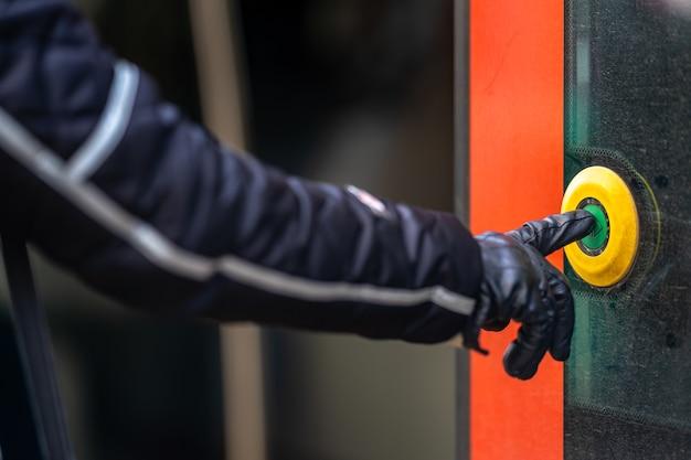 A mão pressiona o botão de abertura da porta no transporte público