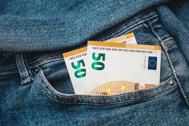 A mão que coloca notas de euro em um bolso de jeans