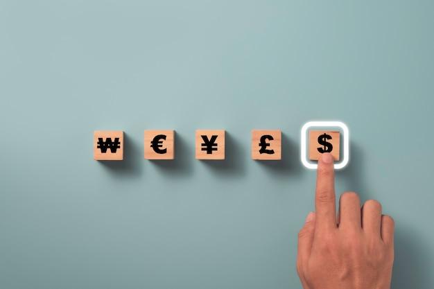 A mão que empurra o bloco de cubos de madeira que imprime a tela do sinal de dólar dos eua com a outra moeda inclui ienes, yuans, euro e won, conceito de câmbio de moeda.