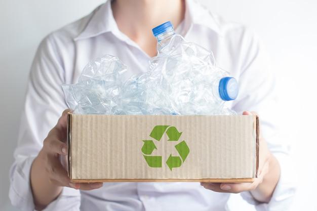 A mão que guarda a caixa de papel marrom com lixo recicla garrafas plásticas.