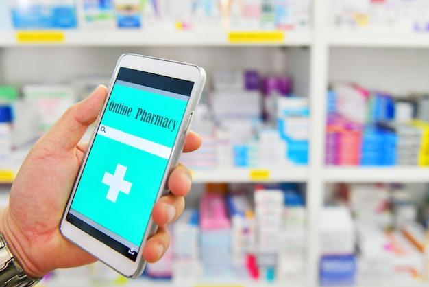 A mão que guarda o telefone esperto móvel para a barra da busca na exposição na drograria da farmácia arquiva o fundo médico em linha.