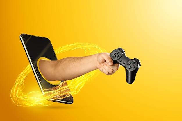 A mão que sai do smartphone segura um controlador de jogo