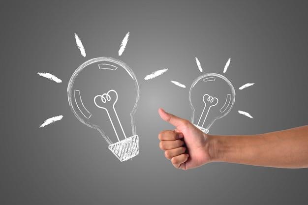 A mão que segura a lâmpada é enviada para a outra mão, escrita em giz branco, para desenhar o conceito.