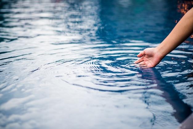 A mão que toca a água azul. a piscina é limpa e clara. com uma gota de água