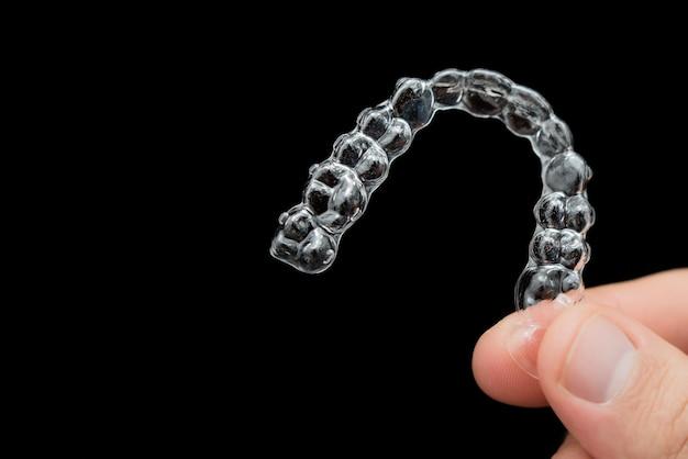 A mão segura alinhadores transparentes, retentores de cintas plásticas em um fundo preto