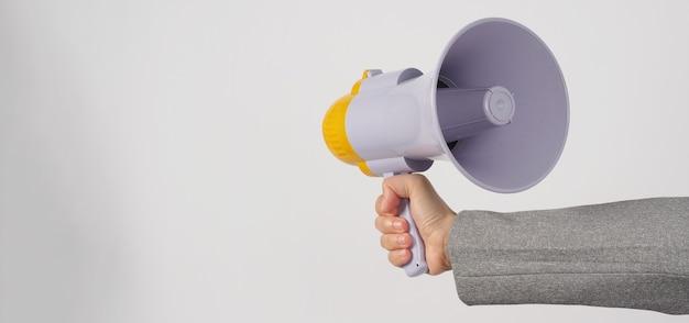 A mão segura o megafone e usa um terno cinza sobre fundo branco.
