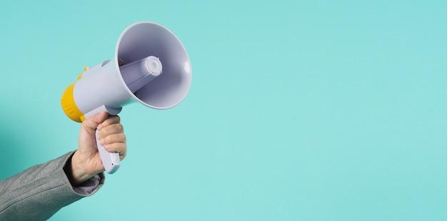 A mão segura o megafone e usa um terno cinza sobre fundo verde, menta ou azul tiffany.