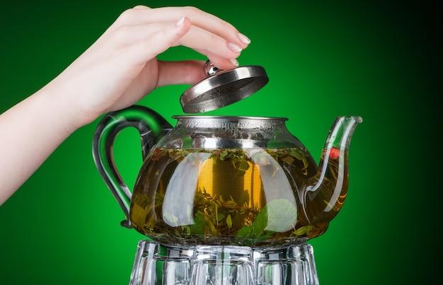 A mão segura um bule de chá transparente com chá de hortelã. isolado com luz de fundo