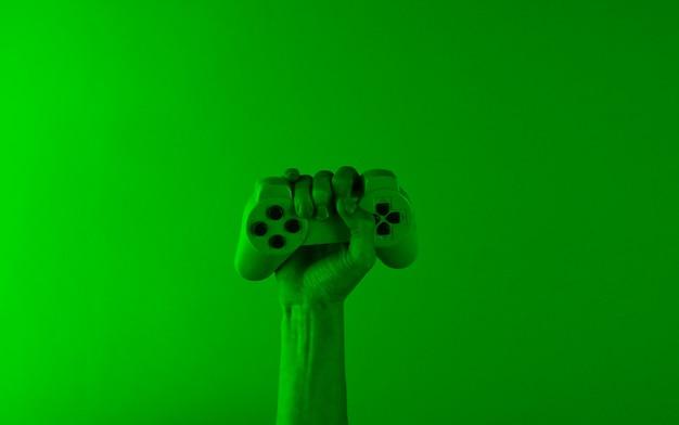 A mão segura um gamepad com luz holográfica verde.