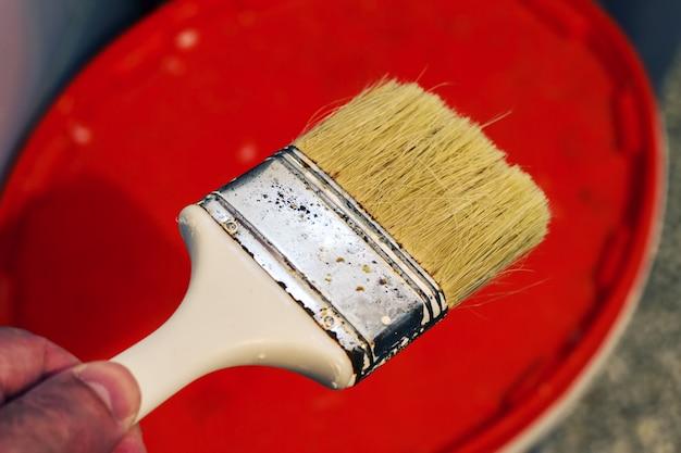 A mão segura um pincel sobre um balde de plástico com uma tinta